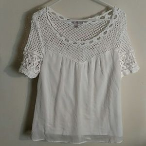 White top with crochet top and sleeve details.